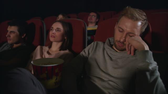 man sleep at cinema movie. guy sleeping at cinema date. people watch boring film - data scritta video stock e b–roll