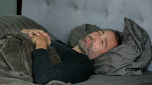 man sleeping in bed video