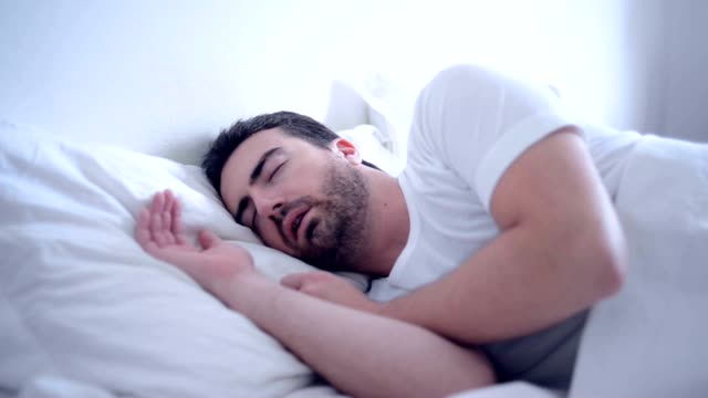 Man sleeping in his bet snoring Man is sleeping in his bed at night and is snoring a lot.Slowly he changes position in the bed and in the end he turned the back to the camera. man sleeping stock videos & royalty-free footage