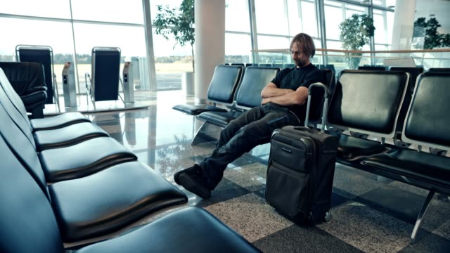 DS Man sleeping in the gate lounge, missing his flight Wide dolly shot of a man sleeping in the gate lounge, missing his flight with no one else around. Shot in Slovenia. seat stock videos & royalty-free footage