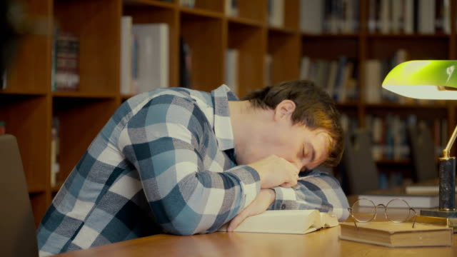 man sleeping on the book Footage portrait of man sleeping on the book. 4k education video yawning stock videos & royalty-free footage