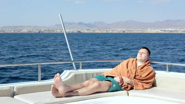A man sleeps at the stern of a yacht.