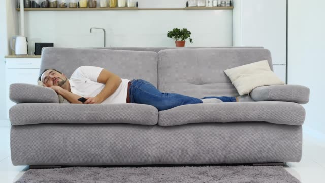 男は灰色のソファーで甘く眠る - 幸運点の映像素材/bロール