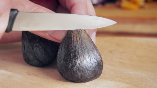 Man Slices Fresh Fig on wooden Cutting Board - 4K video