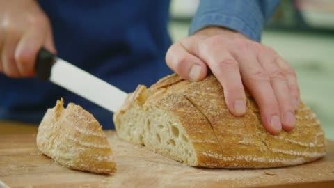 vídeos y material grabado en eventos de stock de hombre crujiente pan con cuchillo de corte en el tablero de corte - rebanada