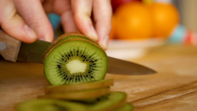vídeos de stock e filmes b-roll de man slicing kiwi with knife on wooden board with fruits and vegetables on background. close-up. - kiwi
