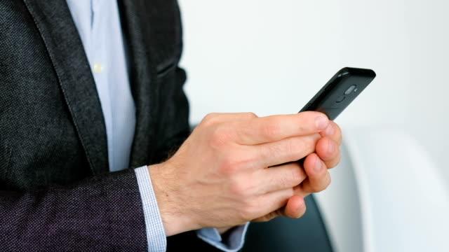 男のスマートフォンは、デジタルアプリは、ビジネスを行うテキストメッセージ - コントロール点の映像素材/bロール