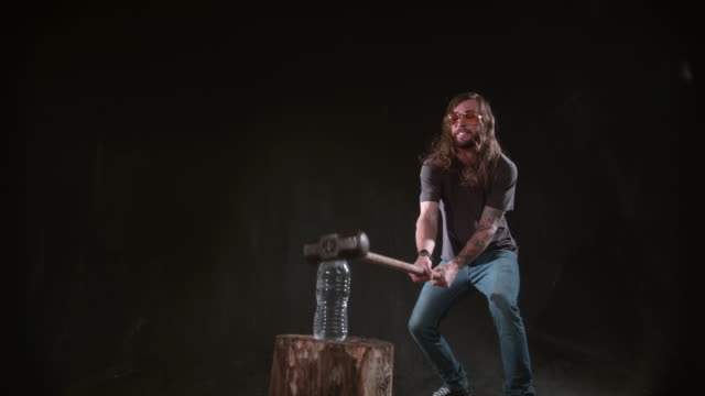 Man smashing bottle of water with hammer in slow motion video