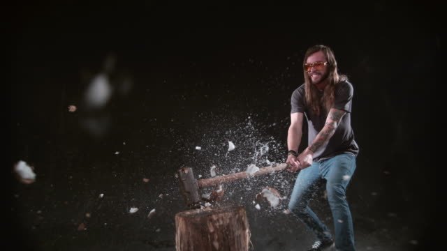 Man smashing coconut with hammer in slow motion video