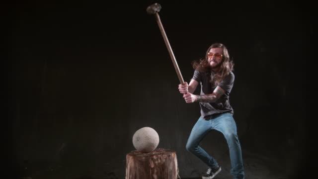 vídeos de stock e filmes b-roll de man smashing melon with hammer in slow motion - triturar atividade