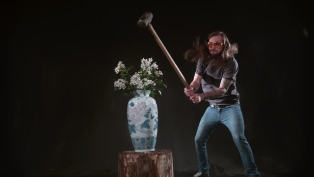 man smashing vase of flowers with hammer in slow motion - zgnieciony filmów i materiałów b-roll