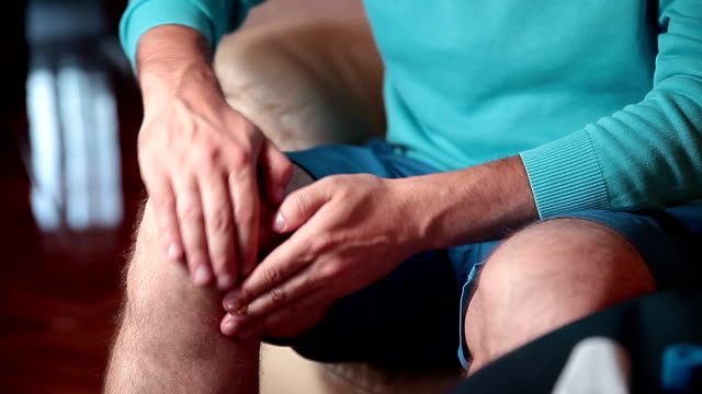 Man smears cream and massages injured knee. video