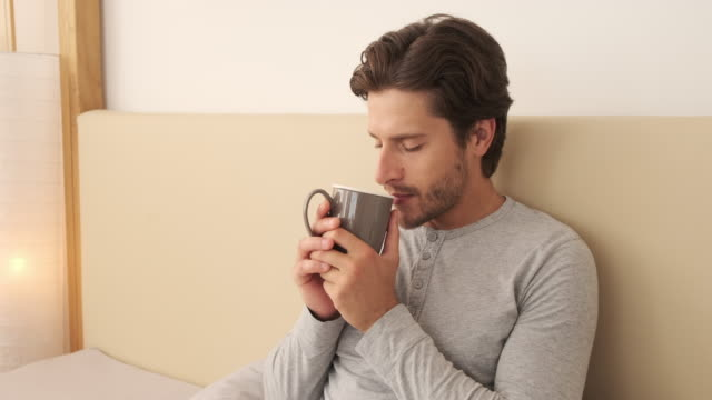 mann riecht und trinkt kaffee im bett - koffeinmolekül stock-videos und b-roll-filmmaterial