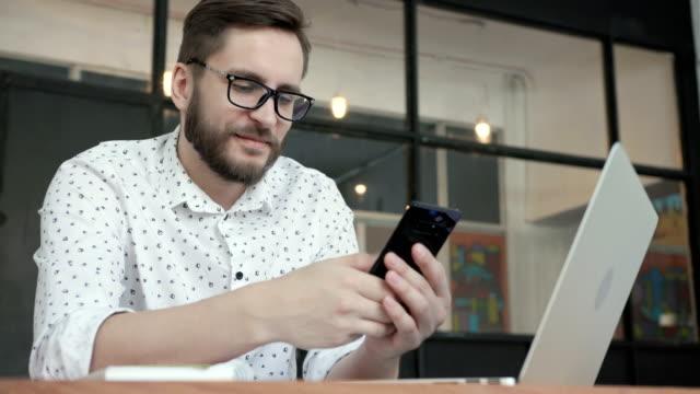 adam gülümseme ve ofiste sohbet için telefon kullanma - sms göndermek stok videoları ve detay görüntü çekimi