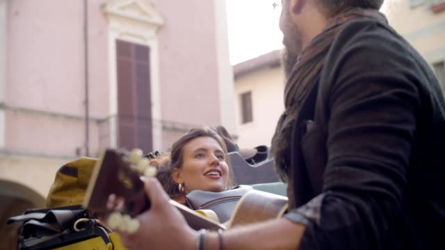 Man smiling while playing guitar music with girlfriend.Woman listening to boyfriend singing song.Caucasian couple in love roadtrip vacation italian travel on convertible vintage car.4k handheld video video