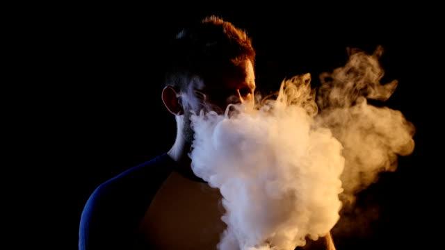 Man smokes an ecigarette, blows smoke through his nose. Black background video