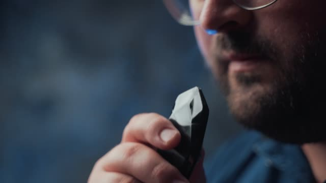 Man smokes new Vape Pod System, inhales and exhales vapor of electronic cigarette, vaping concept video