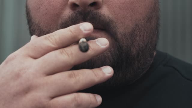 Man smokes real pre-rolled weed joint or medical marijuana or cannabis or hemp, close up video