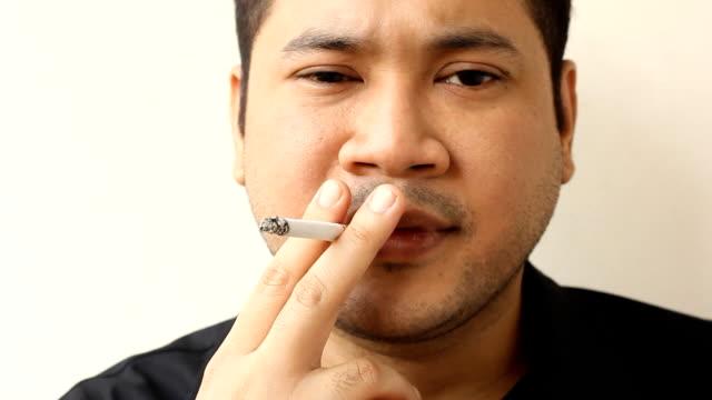 vídeos de stock e filmes b-roll de homem fumar um cigarro - puxar cabelos