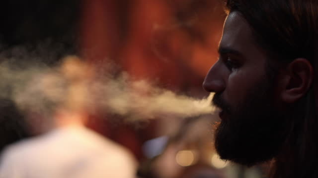 Man smoking cigarette on stage after gig