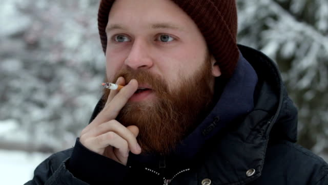man smoking cigarette, young bearded hipster in hat and jacket at forest on natural background video