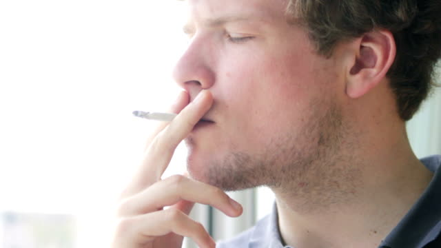 Man smoking hand-rolled cigarette video
