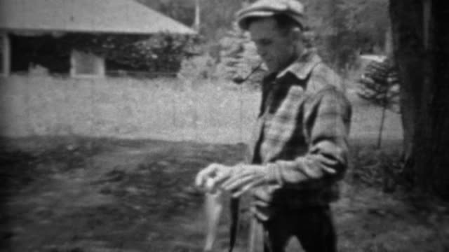1935: Man smoking pipe proudly holding up freshly caught trout fish. video