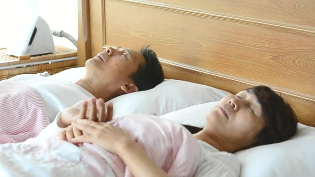 Man snoring swing arm wake his wife up during the night,she pushing him to sleep on his side. video