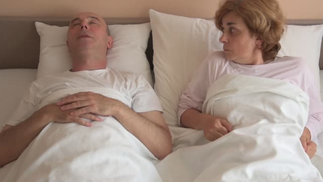 Man snoring while woman cannot sleep