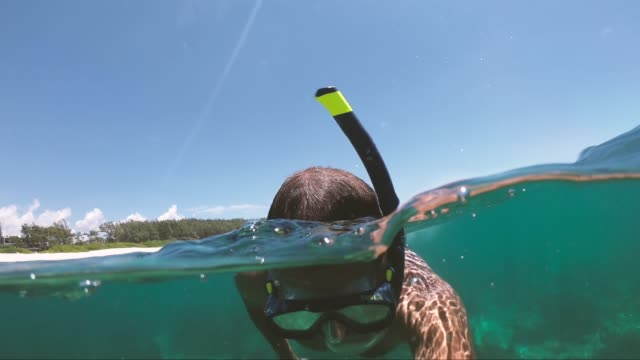 man snorkeling in the beautiful sea of mauritius protected by the reef on the indian ocean - isole mauritius video stock e b–roll