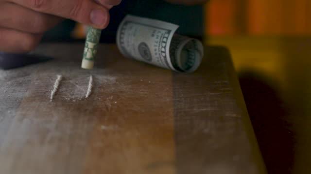 man frustande en rad vitt pulver upp näsan genom en dollarsedel - amfetamin pills bildbanksvideor och videomaterial från bakom kulisserna
