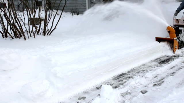 Man snow blowing driveway on cold winter day, medium shot video