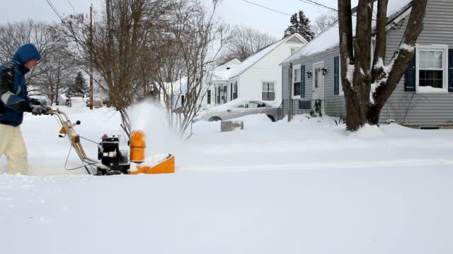 man snow blowing driveway on cold winter day, wide shot - skyffel bildbanksvideor och videomaterial från bakom kulisserna