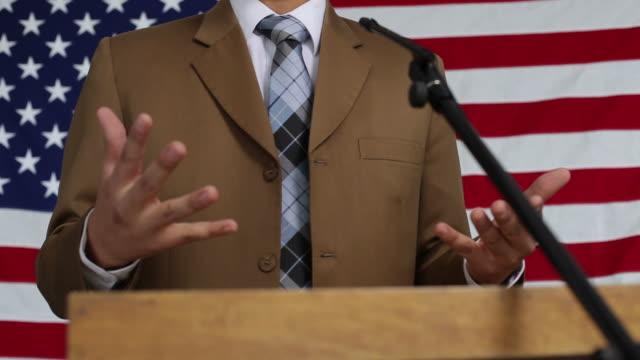 Homme de parler au podium, drapeau en arrière-plan - Vidéo