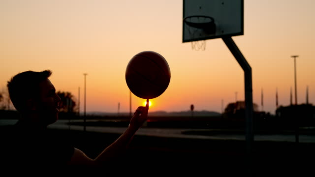 MS SUPER SLOW MOTION man spinning basketball on outdoor basketball court at sunset
