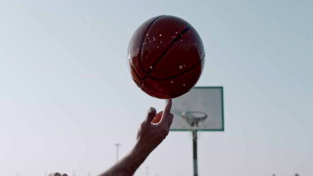 CU SUPER SLOW MOTION man spinning wet basketball on finger