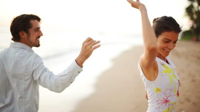 man spins woman on a beach - flörta bildbanksvideor och videomaterial från bakom kulisserna