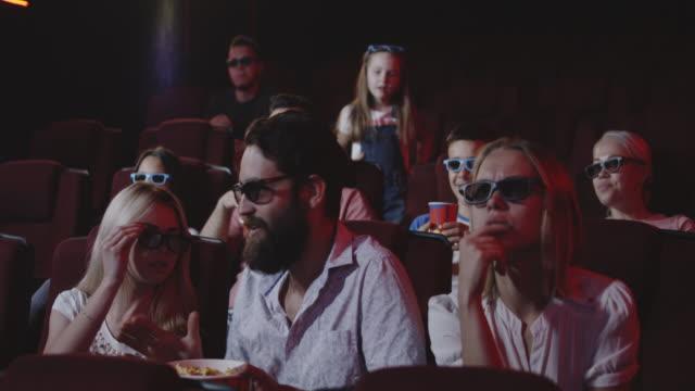 man spoiling movie for fellow moviegoers in cinema - spoiler filmów i materiałów b-roll