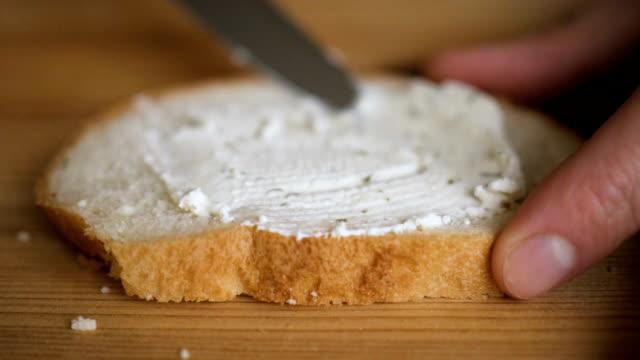 der mensch verteilt butter auf roggentrocken-toast mit einem messer. person, die cremige butter auf einem stück brot verteilt. nahaufnahme der männlichen hände verteilen butter auf brot in der küche, zeitlupe. - quark stock-videos und b-roll-filmmaterial
