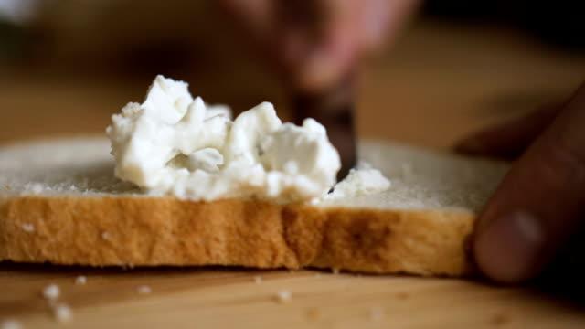 mann auf roggen trockenen toast butter mit einem messer zu verbreiten. person, die cremige butter auf ein stück brot zu verbreiten. nahaufnahme von männlichen händen butter aufs brot in küche, slow-motion zu verbreiten. - quark stock-videos und b-roll-filmmaterial