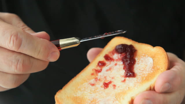 Man spreads jam on buttered toast video
