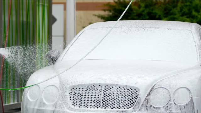 man bevattning dyra elit auto med skummande ämne, biltvätt företag - surf garage bildbanksvideor och videomaterial från bakom kulisserna