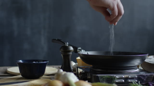 man sprinkling salt on hot pan - посыпать стоковые видео и кадры b-roll