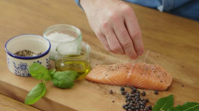 man strör kryddor över rå fiskfilé av ingredienser - marinad bildbanksvideor och videomaterial från bakom kulisserna