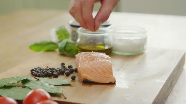 man strör kryddor över rå fiskfilé för marinad - marinad bildbanksvideor och videomaterial från bakom kulisserna