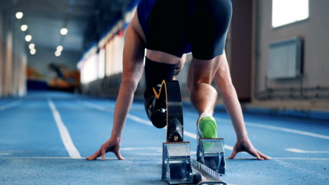 A man sprints, wearing prosthetic leg, back view. Person runs on a track with a leg prosthesis. prosthetic equipment stock videos & royalty-free footage