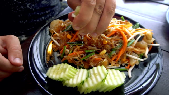 Man Squeezing Lime into Asian Noodle Dish Slow Motion video