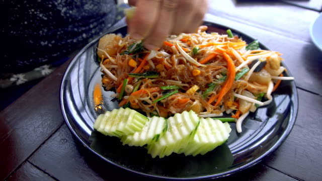 Man Squeezing Lime into Asian Noodle Dish video