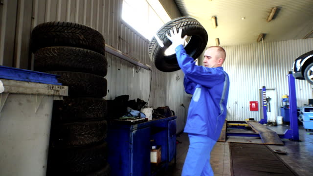 Man stacking worn tires in garage. tire changing and storing services. video