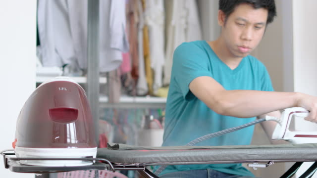 Man stand and ironing clothes in the living room Man  stand and ironing clothes in the living room, Taking chores during the day, realtime footage, laundry basket stock videos & royalty-free footage
